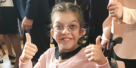 A girl smiles whilst facing the camera with her thumbs up. She wears glasses.