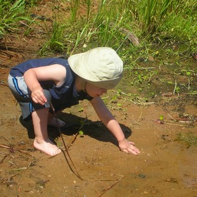 baby playing in a stream